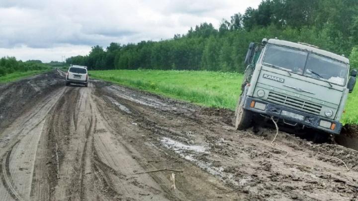 КамАЗ застрял в грязи на трассе под Новосибирском