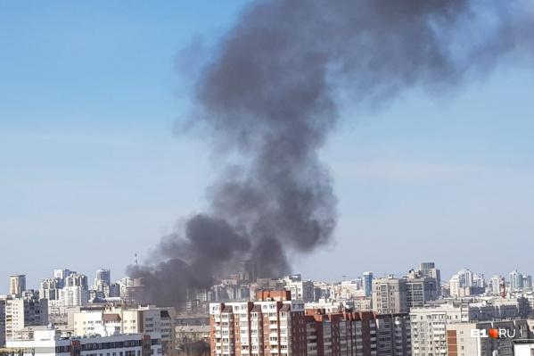 Черный дым в чистом небе над городом видно издалека