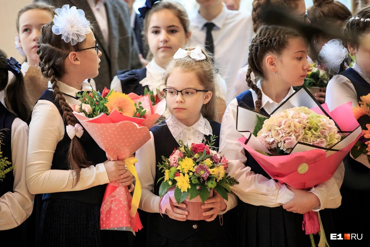 Дети с букетами ждут, когда можно будет вручить их учителям