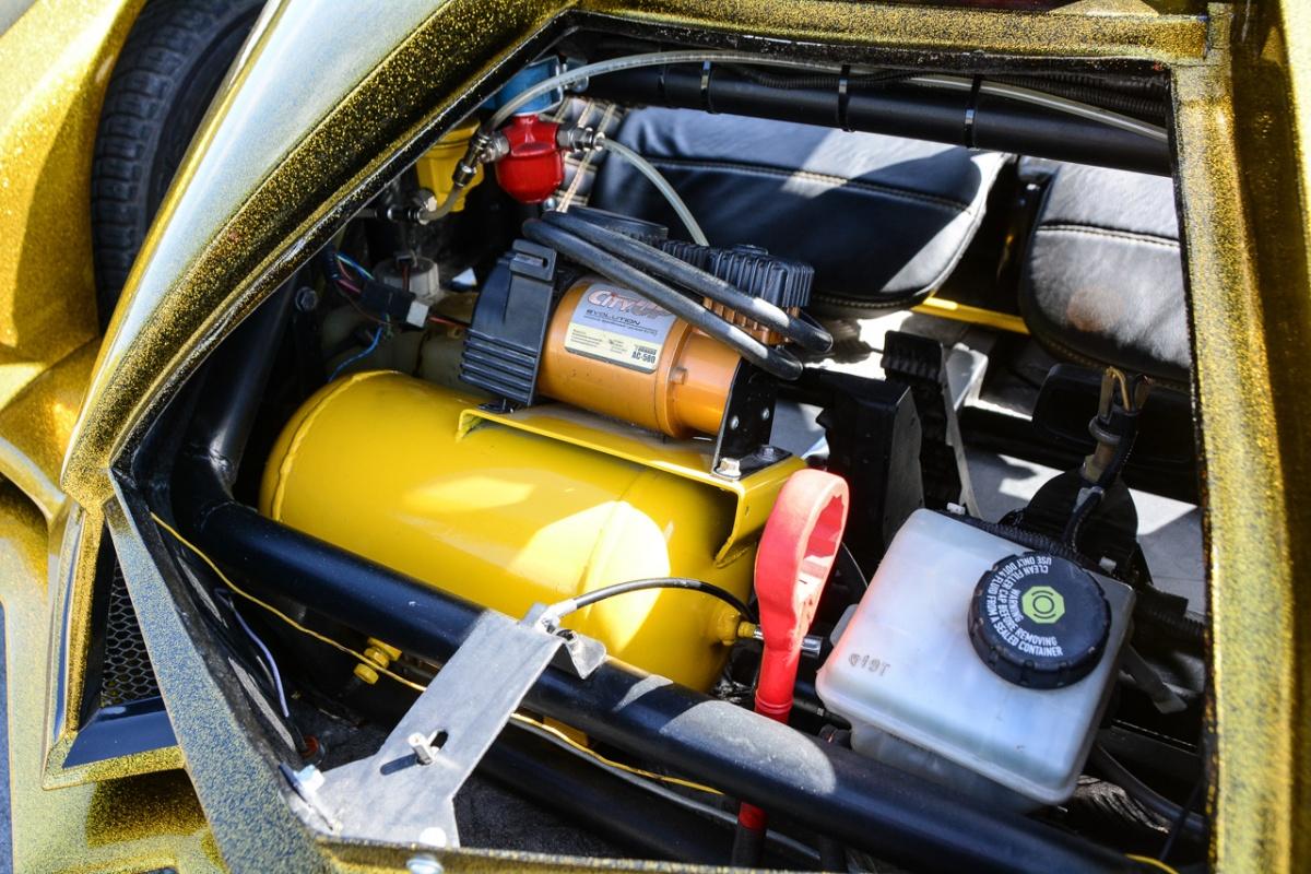 Под крышкой в передней части трайка — компрессор и пневмобаллон. Клиренс регулируется в небольших пределах