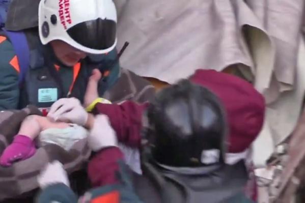 Спасатель Пётр Гриценко передаёт малыша врачу Анатолию Чумичёву