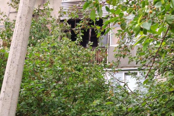 Выбитые пожаром окна на балконе сгоревшей квартиры