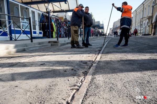 Рабочие убирают лишний асфальт ломом