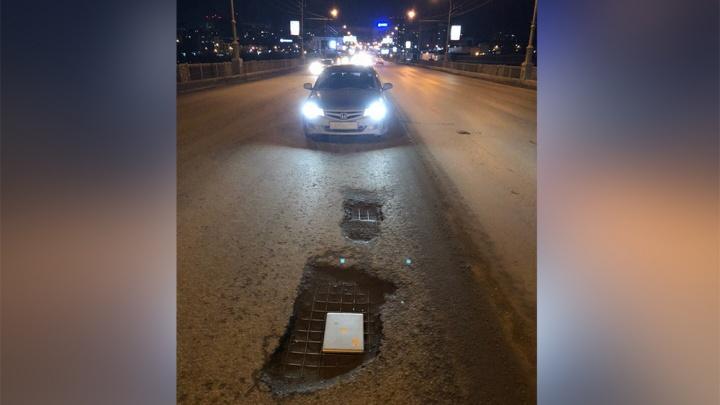 «Чуть на встречку не выкинуло»: машина влетела в яму на Октябрьском мосту и пробила два колеса