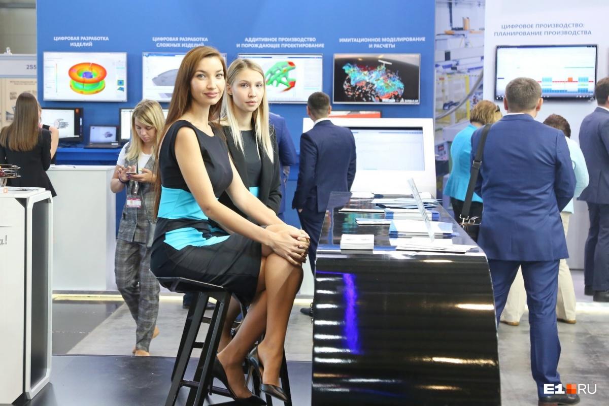 Девушка слева в прошлом году участвовала в конкурсе «Мисс Екатеринбург», а в этом году украшает собой стенд Минпромторга