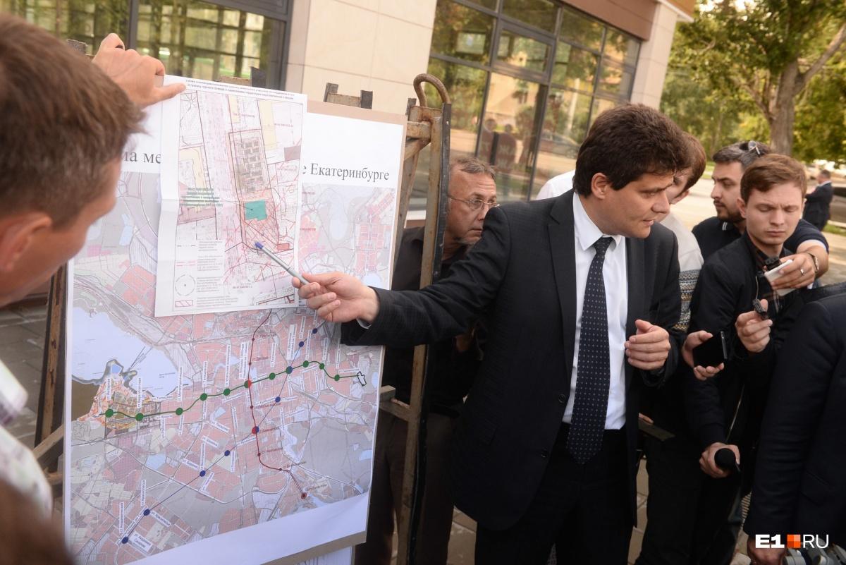 Мэр Александр Высокинский показывает, что офисник мешает строительству будущей станции