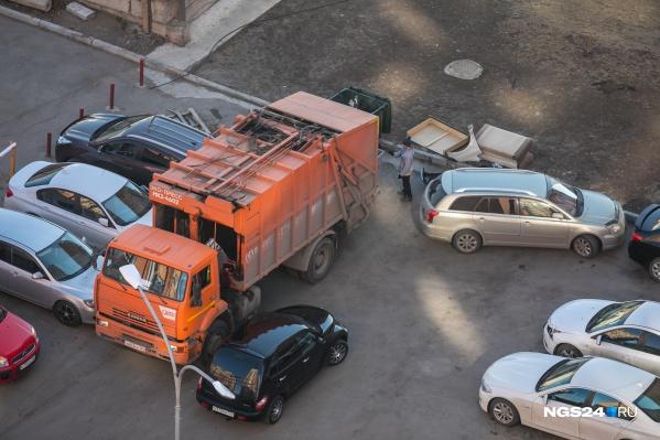 Мусоровоз выгружает отходы из контейнеров во дворе Красноярска