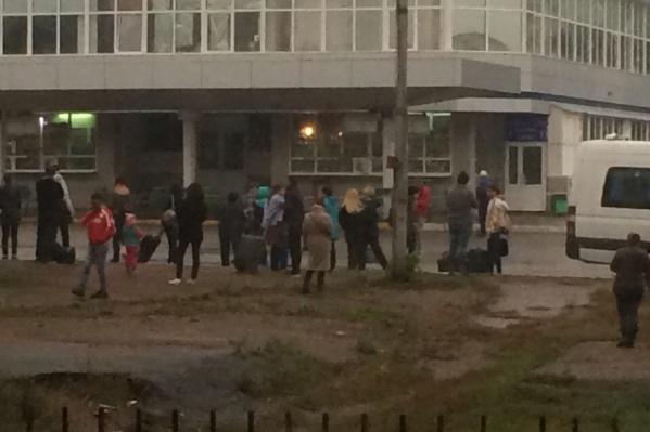 Десятки людей стоят на улице