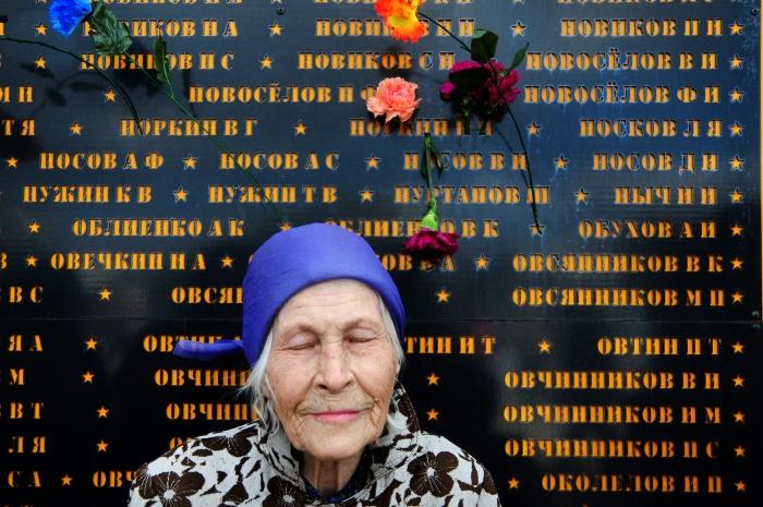 Наталья Петровна на фоне мемориала, на котором высечено имя ее потерянного брата