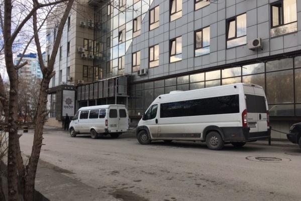 Возле здания стоят два тонированных микроавтобуса