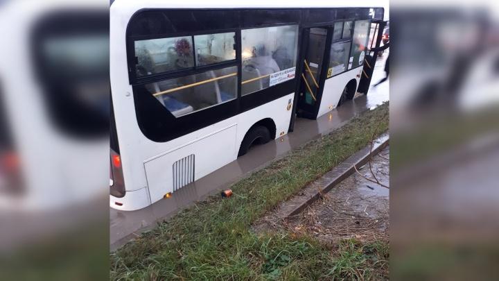 Автобус, застрявший в яме на Мельникайте, вытаскивали с помощью самосвала