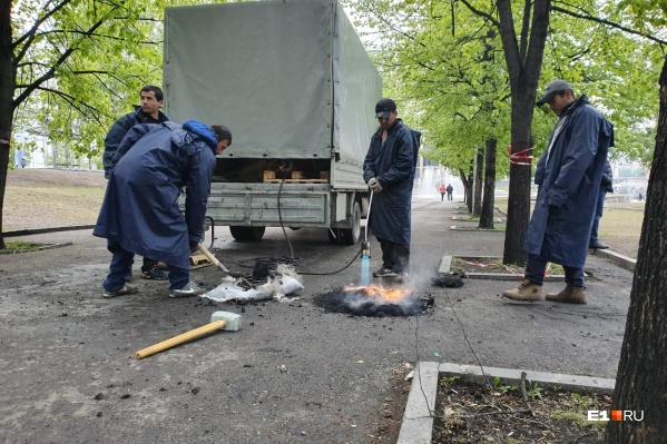 Рабочие латают дыры в том месте, где стояли опоры забора