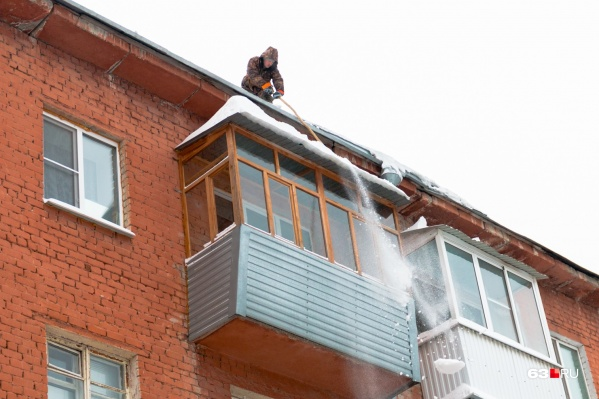 Иногда рабочие помогают жильцам почистить козырьки балконов