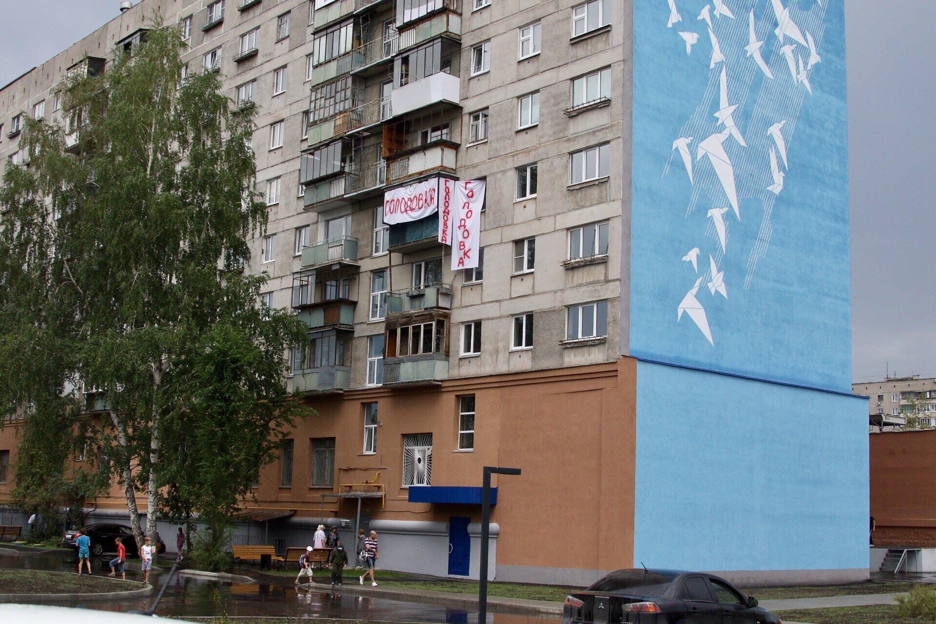 С одной стороны дома на Карла Маркса, 164 теперь памятные граффити, а с другой — растяжка о голодовке
