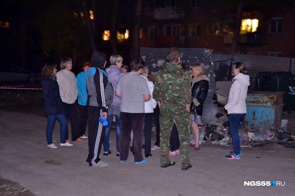 Жители многострадального дома столпились у участка, огороженного лентами: они окружили представительницу администрации Советского округа