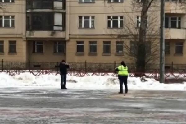 Мужчина в спецжилете на камеру посыпал тротуар