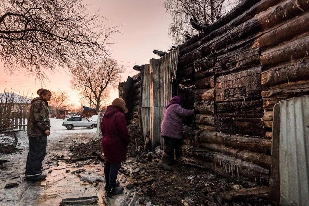 Местные жители приходят на пепелище, оглядывая то, что осталось от дома Евсюковых