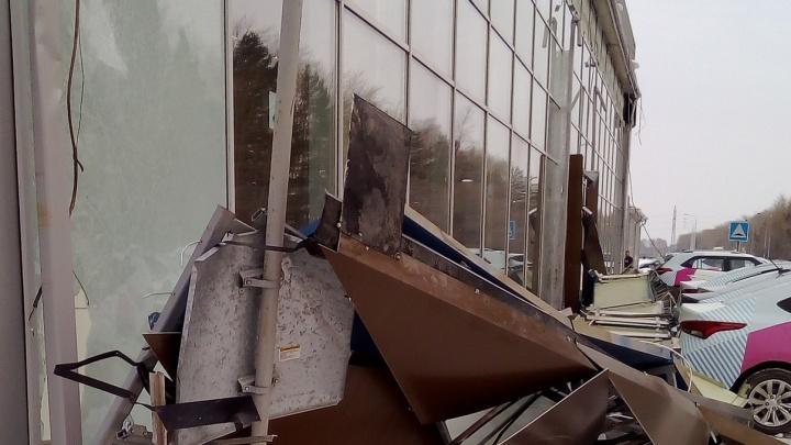 Металлическая вывеска упала на припаркованные машины автоцентра в Тюмени