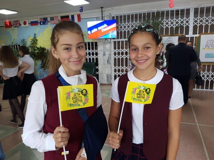 Вместо традиционных букетов школьники держали в руках флажки акции