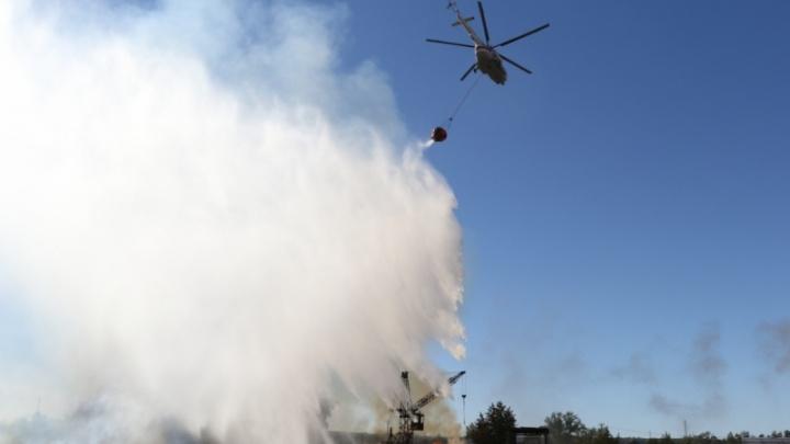Вспыхнувший склад бревен тушили вертолетами и пожарным поездом спасатели