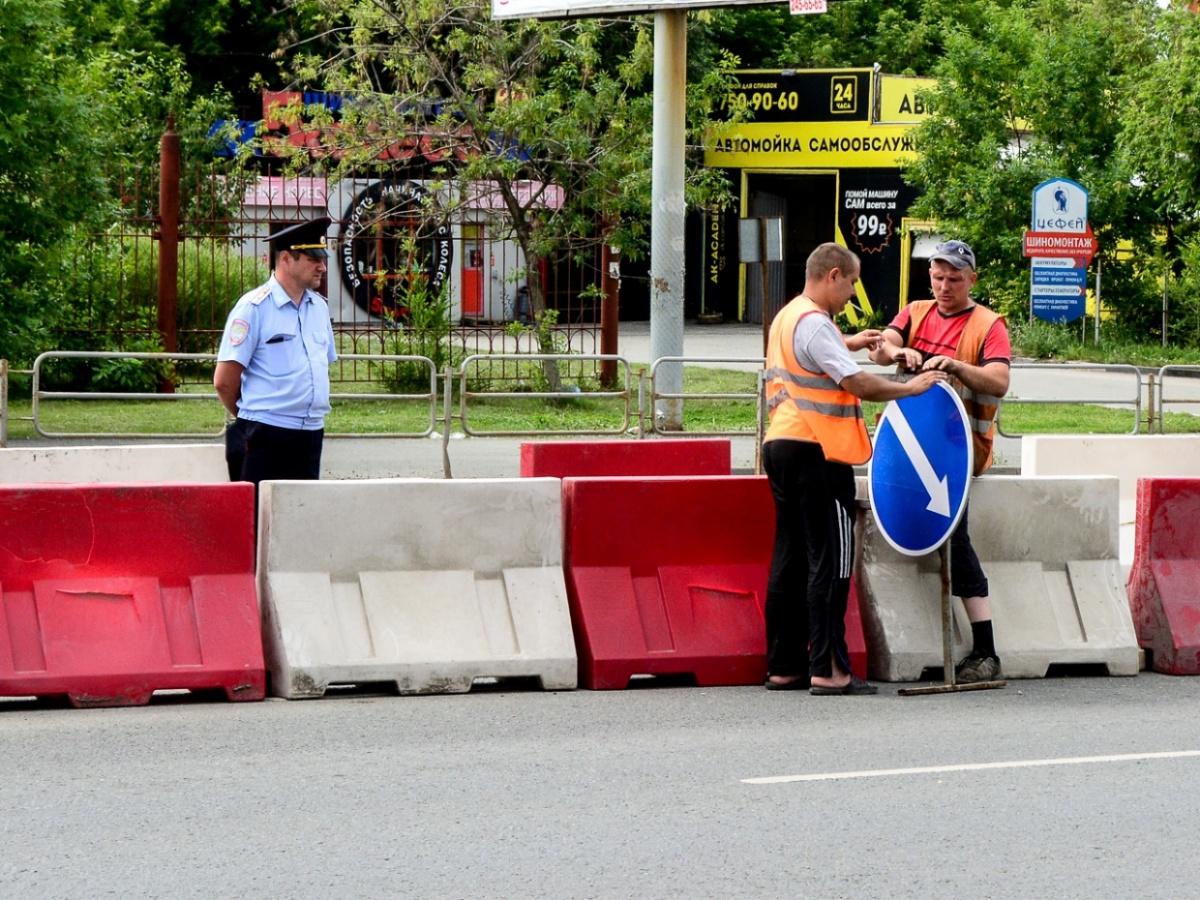 Рабочие устанавливают временный знак, показывающий направление объезда препятствий: он имеет приоритет над разметкой