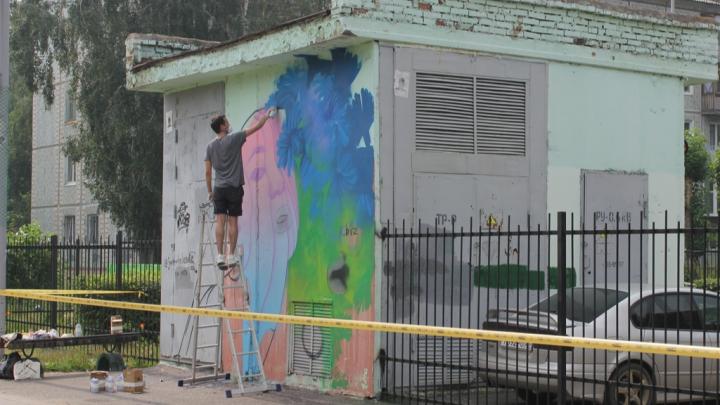 На левобережье художник начал рисовать девушку в цветах на стене трансформаторной будки