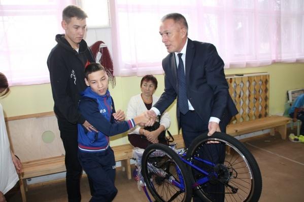 Судя по фото, ребенок, который получил велосипед, не может самостоятельно стоять