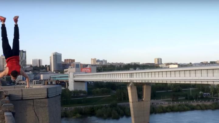 Акробат в красной майке встал на руки на краю Октябрьского моста