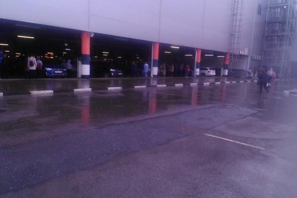 Эвакуированные люди прятались от проливного дождя на крытой парковке