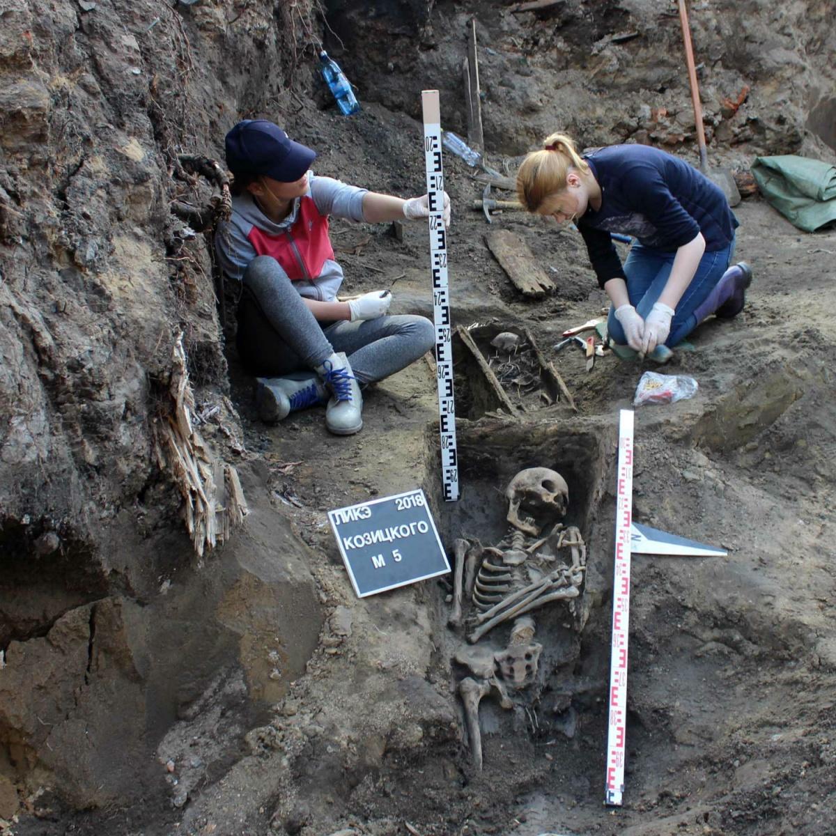 Над скелетом взрослого человека можно разглядеть небольшой гробик с останками поменьше