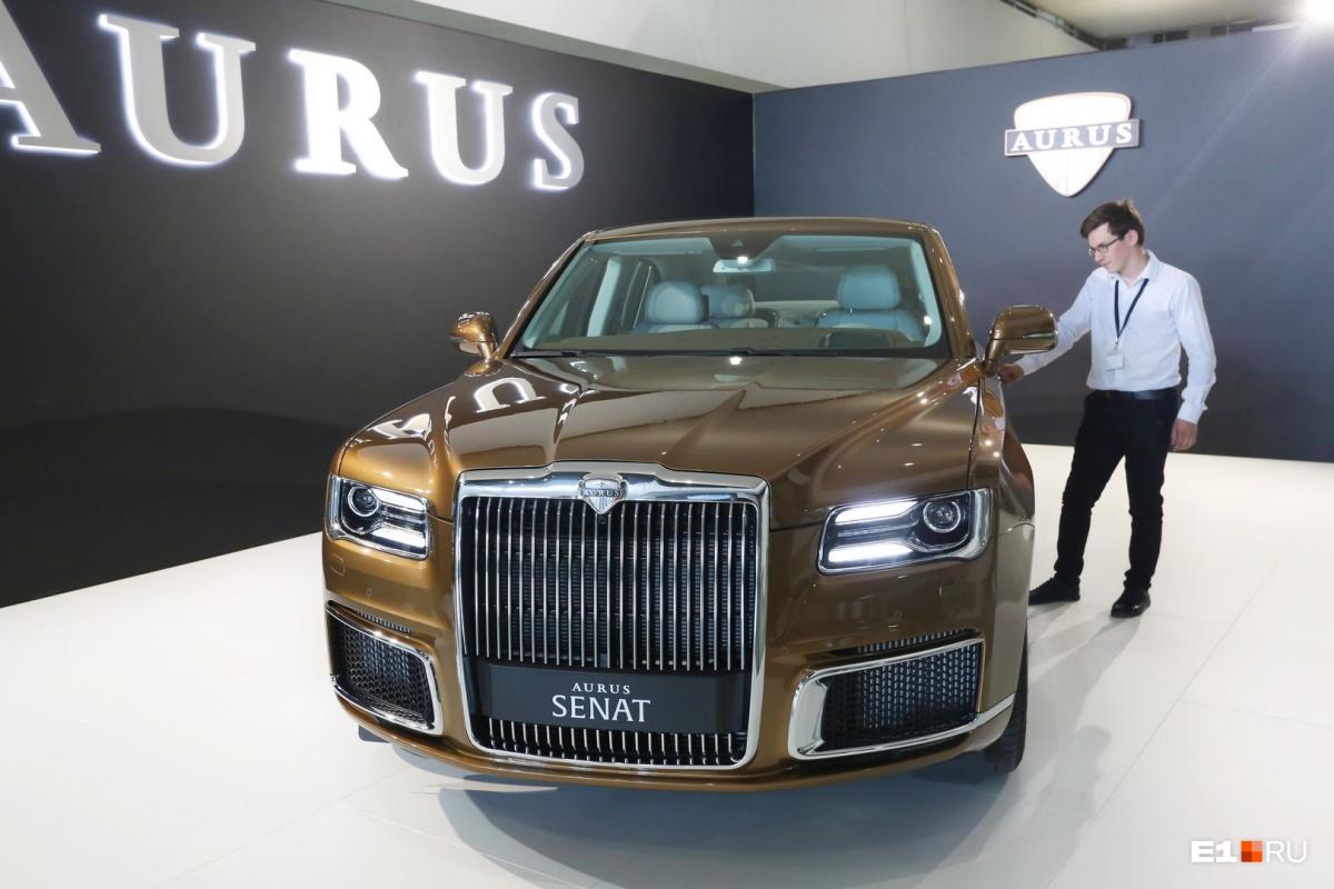 На стенде НАМИ показывают российский автомобиль представительского класса Aurus Senat, на котором ездит президент Владимир Путин (только его автомобиль длиннее). На фото: сотрудник компании, охраняющий авто