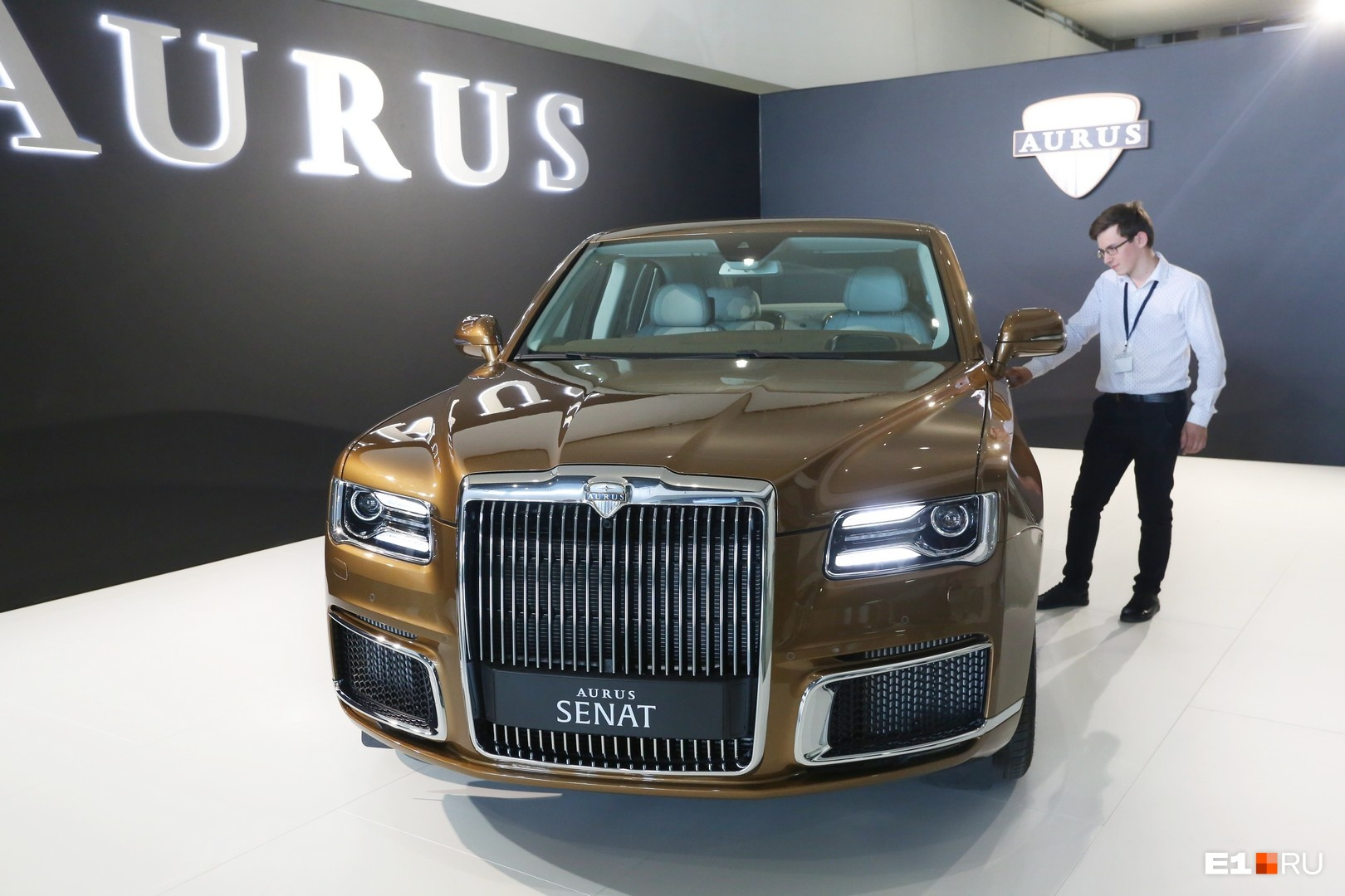 """На стенде&nbsp;<b class=""""_"""">НАМИ&nbsp;</b>показывают российский автомобиль представительского класса Aurus Senat, на котором ездит президент Владимир Путин (только его автомобиль длиннее). На фото: сотрудник компании, охраняющий авто"""