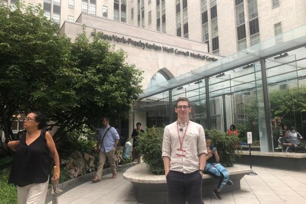 Григорий Тагильцев на фоне центрального входа в Корнелл и New York Presbyterian Hospital