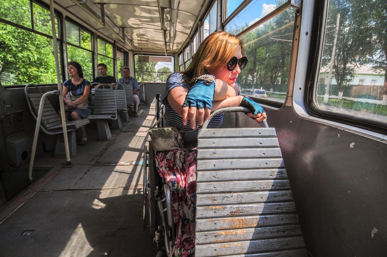 Оля почти не ездит на трамвае, поэтому с любопытством смотрит в окно, на остановках спрашивает, как они называются, и здоровается с пассажирами, которые входят в салон