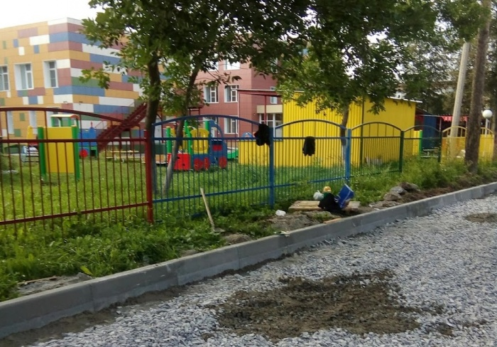 Дорожники работают у ограды садика на улице Тимирязева