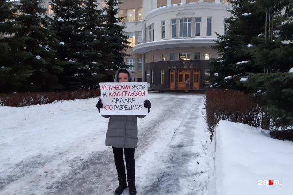 Одна из активисток встала с плакатом около входа в областное правительство