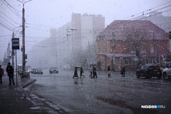 Люди пробираются сквозь пелену снега, закрываясь зонтиками