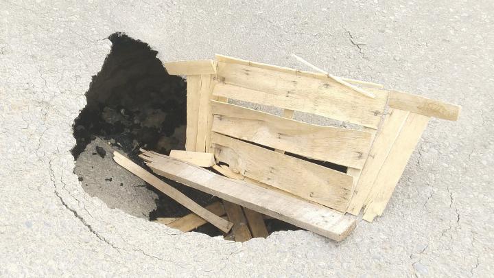 «Везде просто футболят»: метровые ямы на дороге Волгограда прикрыли хлипкими заборчиками