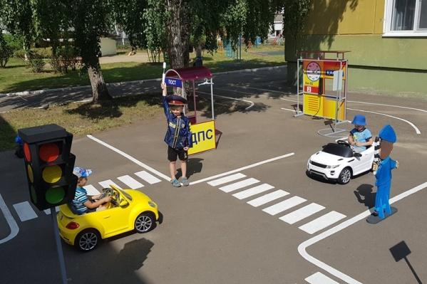 На миниатюрной дороге малыши учат правила вождения