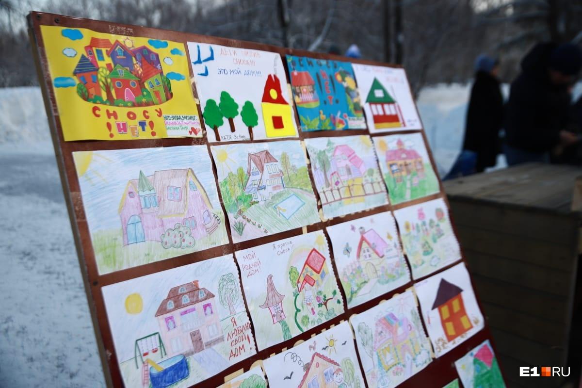 На митинг принесли рисунки детей, которые нарисовали домишки и деревья под солнцем