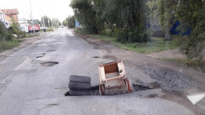 Заткнули ямы креслом: омичи пожаловались на разбитую дорогу по улице Вавилова