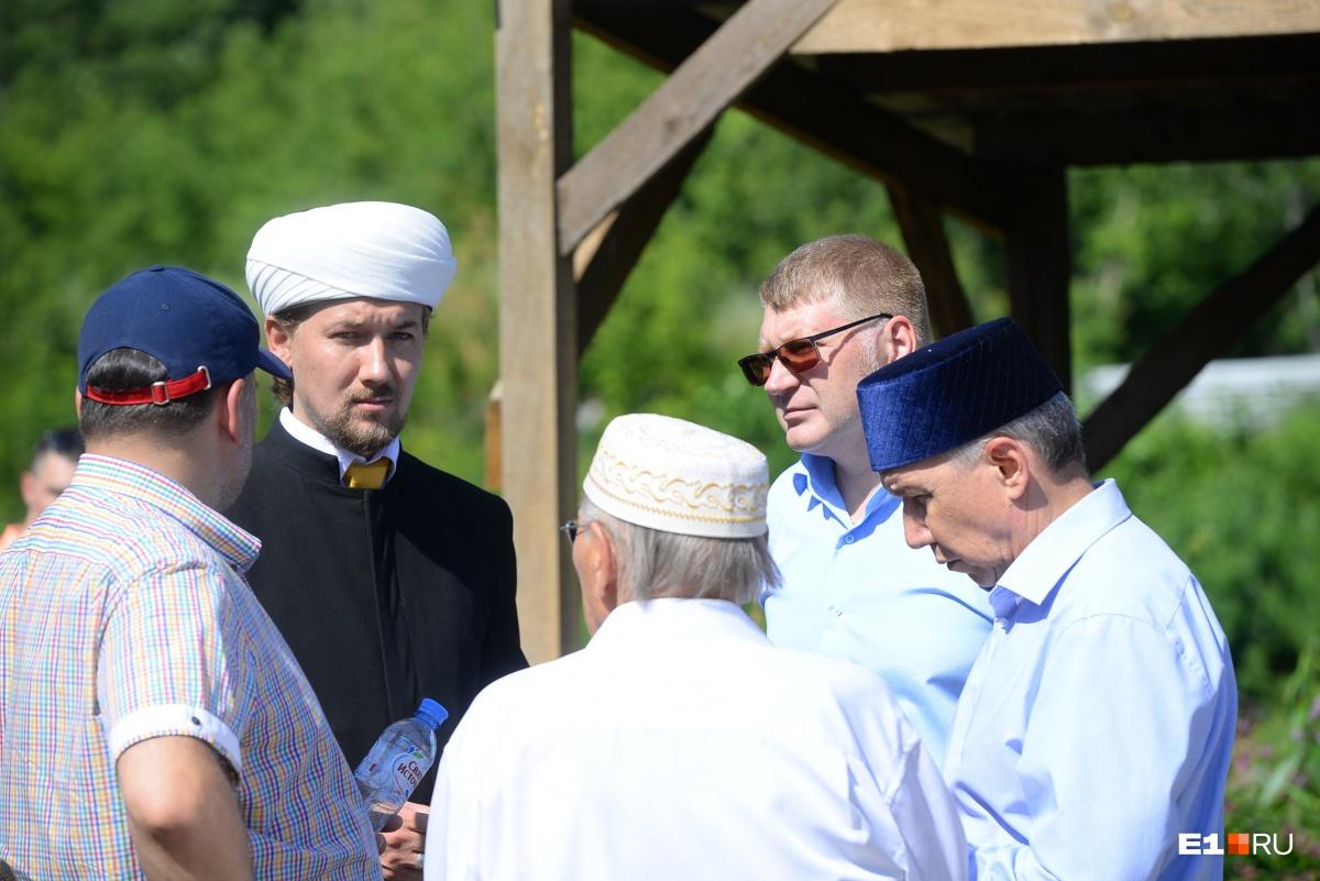 Слева — имам временной мечети
