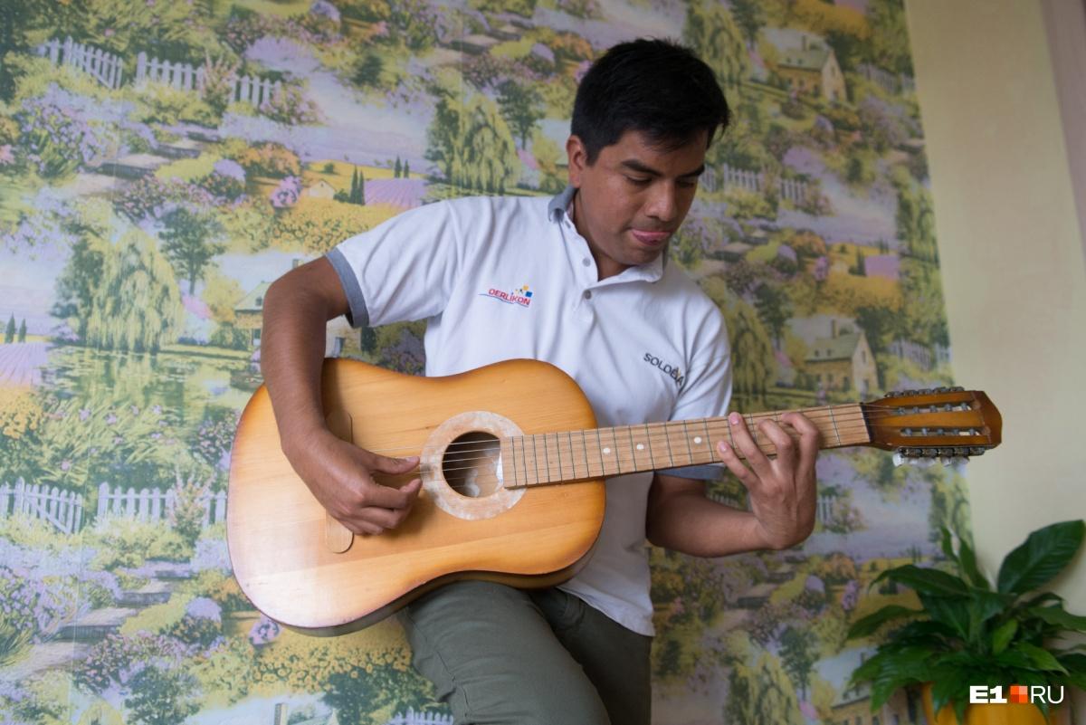 Играет на старенькой гитаре и учит русские песни
