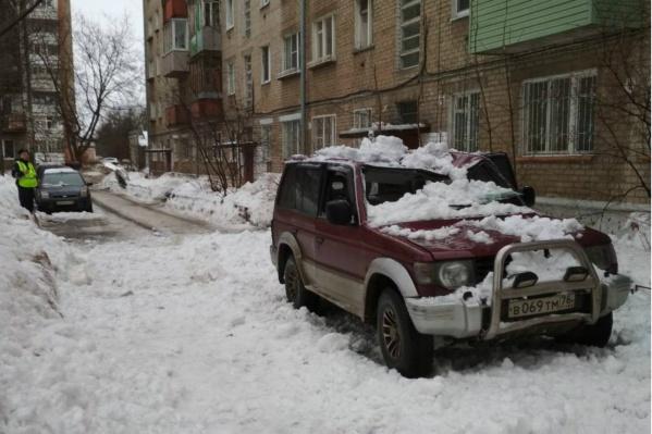 Рухнувший снег смял крышу машины