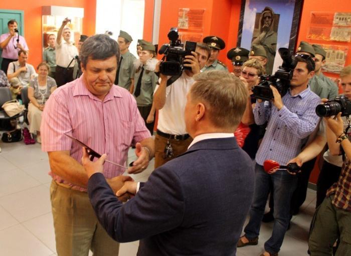 Мэр Новосибирска Анатолий Локоть вручает Виктору Кротенко вкладыш из смертельного медальона его деда
