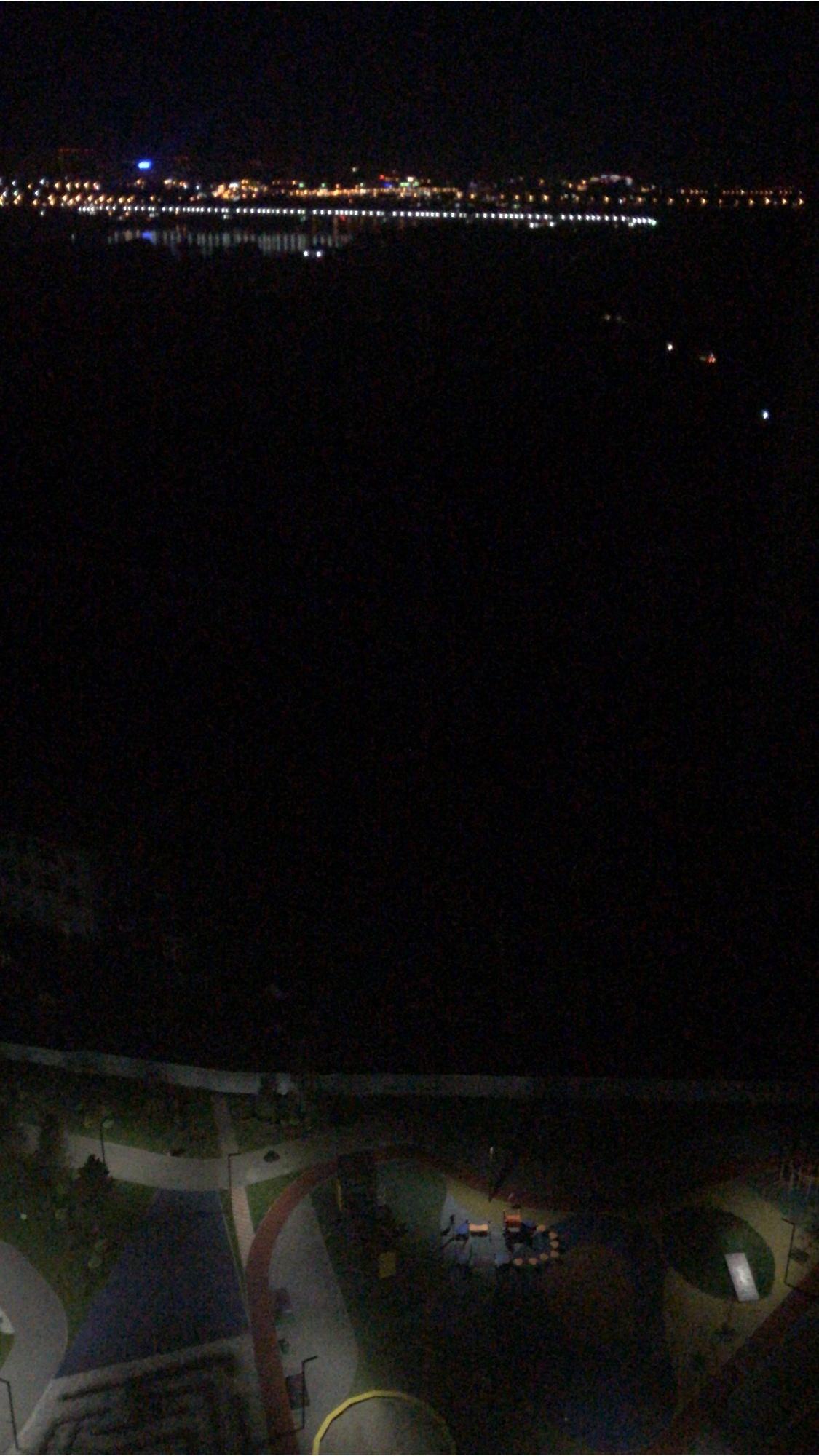 Фотография, сделанная с верхнего этажа одного из домов левобережья: внизу — детская площадка, вверху —огни правого берега, а между ними —чёрная пустота