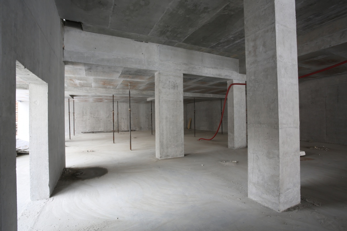 На площадке проводятся масштабные работы: строители бетонируют фундаментную плиту первой секции, возводят вертикальные конструкции