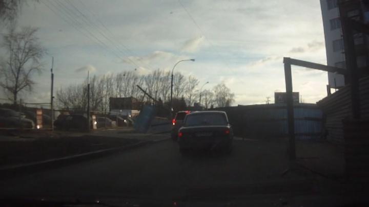 В Екатеринбурге рабочие сломали металлический забор о проезжавшую мимо машину