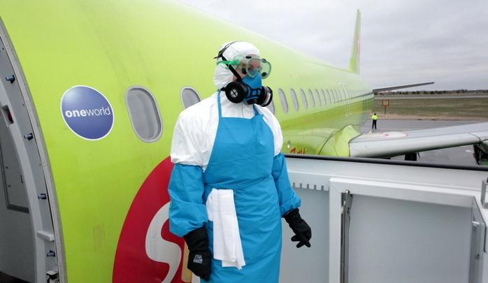 В Толмачёво люди в респираторах и халатах подкатили к самолёту носилки