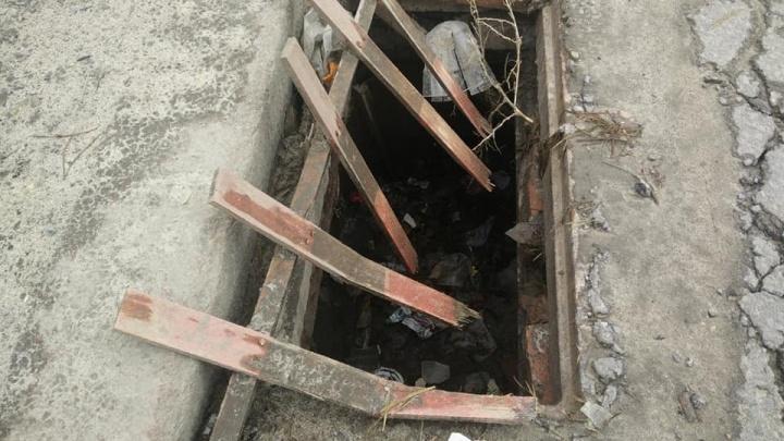 «Упадет ребенок — разобьется насмерть»: трухлявыми досками прикрыли ливневки на дороге в Волгограде